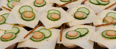 Bread rolls with slices of cheese served with sliced cucumber Reklamní fotografie