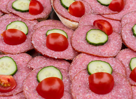 Rolls with slices of sausage topped with sliced cucumber and tomato Reklamní fotografie