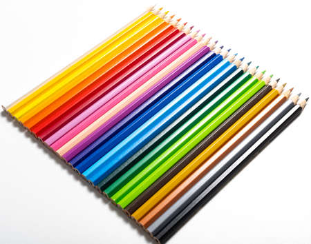 Colored pencils of different colors lined up on white background