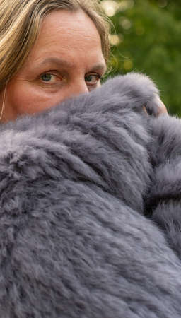 Woman in a rabbit fur jacket during a photo shoot in a city park