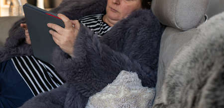 Woman in a rabbit fur jacket works with a tablet PC in the home office Standard-Bild