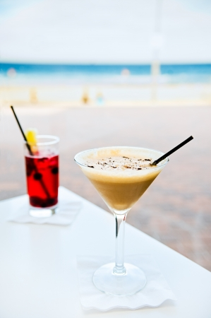 Two glasses of cocktail on a beach background photo