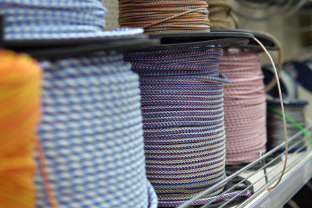 A miscellaneous purpose colorful ropes in bobbins on shelfs in the construction materials store.