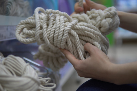 Close up hands hold cotton tightrope, human chooses and buys a white rope in supermarket in department of household goods. 版權商用圖片