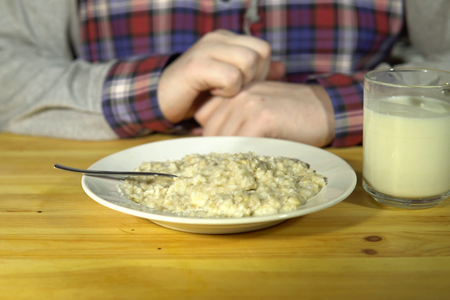 A white plate of oatmeal and a mug of milk stand on a wooden table in front of a washed-out unknown man in a plaid shirt.