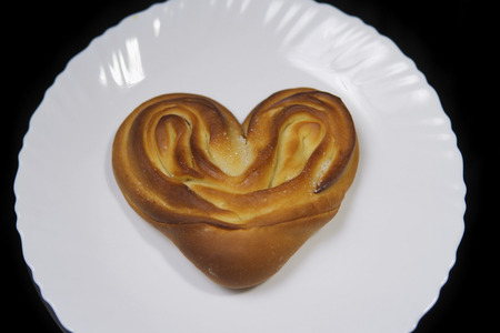 Top view of a heart shaped bun, baking lies on a white plate on a black background.