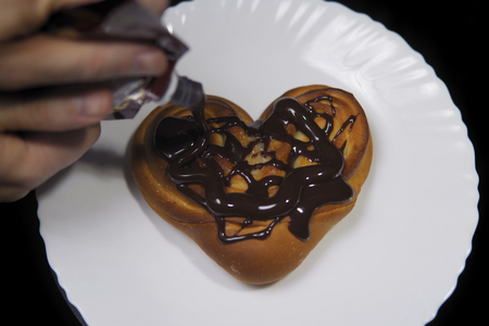 Someone pours chocolate on a sweet heart-shaped bun, fresh baking lies on a white plate on a black background, top view.