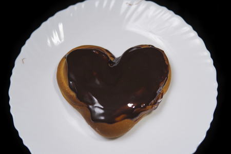 Top view of a heart shaped bun chocolate covered, baking lies on a white plate on a black background.