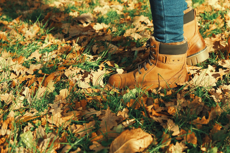 Legs in blue jeans and brown boots, in autumn or winter goes for a walk on dry fallen oak leave, side view. Imagens