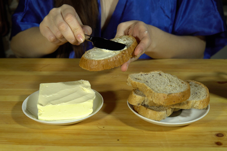 A young woman in a blue smock spreads butter on a slice of multigrain bread, the brunette sits next to a brick wall, 4K. Imagens