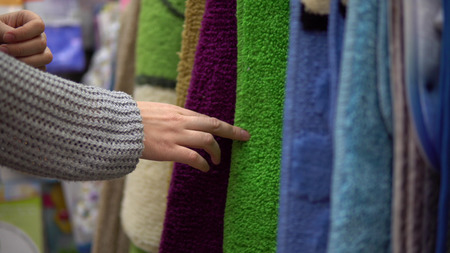 Female hands touch colored mats to choose new carpet for bath or bedroom in the store, place for text. Imagens