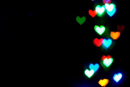 Blurred heart shaped bokeh, blue, red, green, yellow lights on black background