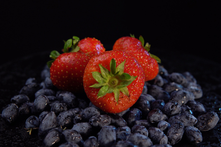 Dark honeysuckle berries and sweet strawberries against black background, place for text. Concept of healthy and proper nutrition. Imagens