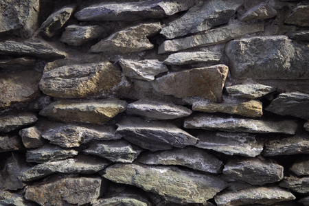 Old grey granite wall built of ancient stonework, abstract background with place for text. Imagens