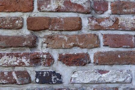 Old wall with ancient crumbling brickwork, you can see the structure of the bricks, abstract background with place for text. 写真素材