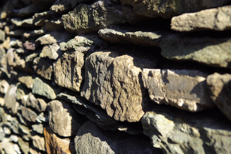 Old grey granite wall built of ancient stonework, abstract background with place for text and selective focus. Imagens