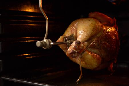 Chicken is spinning on spit under fire large long gas burner in home furnace. Cooking bird in oven for special dinner.