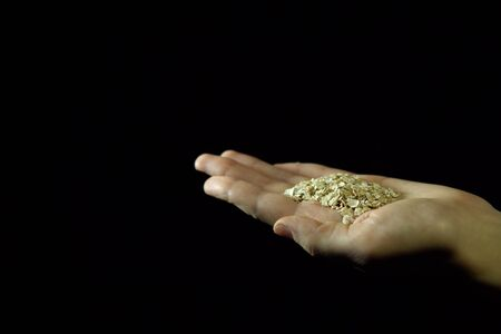 Close-up of human hand holding handful of oatmeal in the palm of hand against black background, space for text.