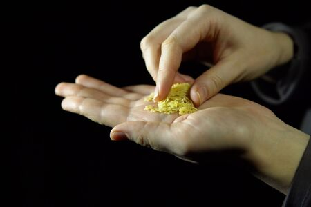 Close-up of human fingers touches handful of macaroni in hand on black background, unrecognizable person.