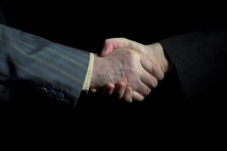 Close-up of of handshake of businessmen on black background. Hand of an elderly man shakes palm of young guy, place for text.