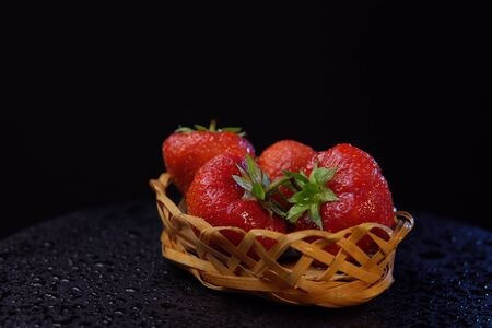 Ripe wet ugly strawberries with green leaves in small basket on black background,place for text. Imagens