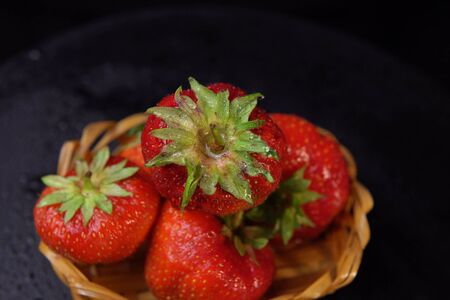 Top view of wet red berries. Ripe strawberries with green leaves in small basket on black background.