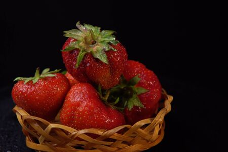 Side view of wet ugly strawberries. Ripe red berries with green leaves in small basket on black background,place for text and selective focus.