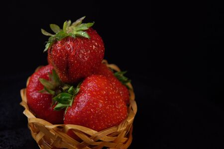 Side view of wet ugly strawberries,place for text and selective focus. Ripe red berries with green leaves in small basket on black background. Imagens