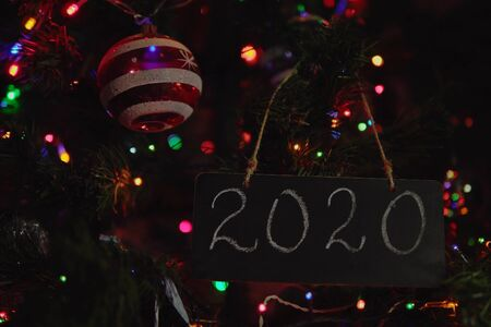 Chalky black plaque with a white number 2020 on the Christmas tree among the lights and balls 写真素材