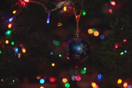Blue xristmas ball with a silver snowflake weighs on branch of festive artificial Christmas tree among the colorful lights of garlands. 写真素材