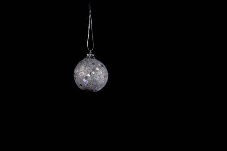 Silver Christmas tree ball with sequins on a black background.Copy space for text.