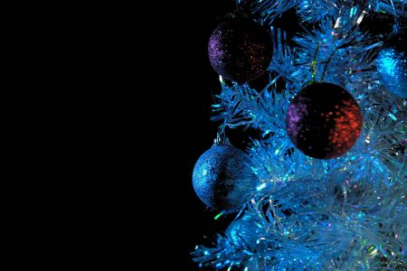 Close-up of shiny white and red balls hanging on a silver artificial Christmas tree in the rays of blue lighting on a black background, selective focus and place for text .