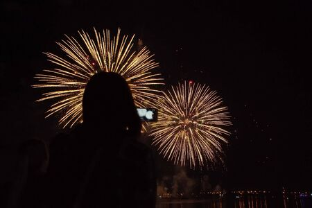 Silhouette of a young woman with a smartphone against the background of bright Golden sparks of fireworks in the black sky. Girl records video camera gadget about the holiday.