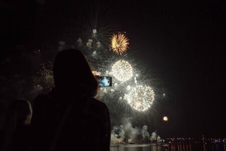 Silhouette of a girl with a smartphone on the background of bright colorful fireworks in the black sky. Banque d'images - 135503266