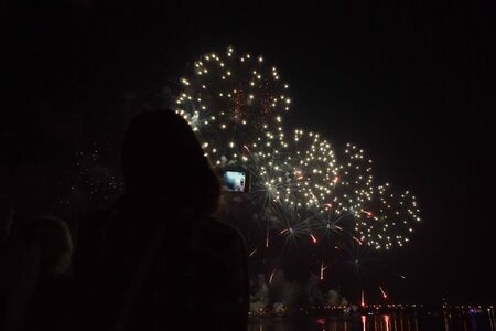 Young woman captures videos with your smartphone camera on holiday.Silhouette of people against the background of bright golden sparks of fireworks in the black sky.