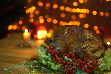 Roasted bird on platter with salad stands on a table amidst yellow electric lights with a festive Christmas dinner .