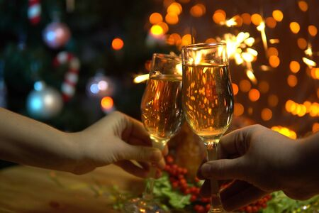 Close-up of a female and male hand holding champagne glasses against a background of burning sparklers and electric garlands on Christmas evening
