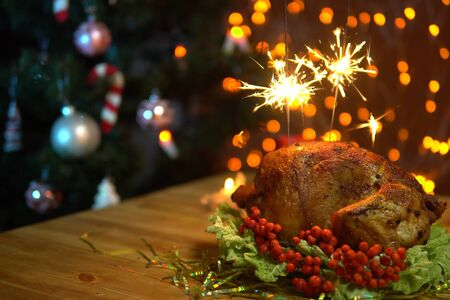 Roasted delicious chicken on a plate with salad with burning sparklers against the background of the garland and Christmas tree on a festive evening.