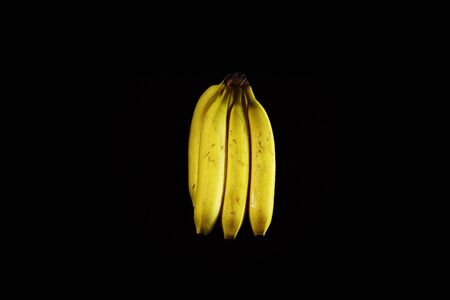 Bunch of yellow ripe bananas with drops of water on black background, copy space. 写真素材