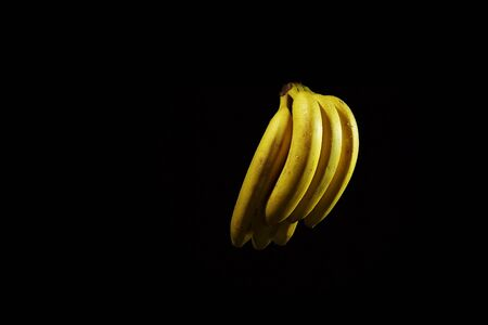 A bunch of yellow ripe bananas with drops of water on a black background, wet fruits with place for text. 写真素材