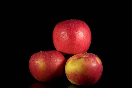 Three ripe red apples with water drops on the sides on a black background, a place for text.