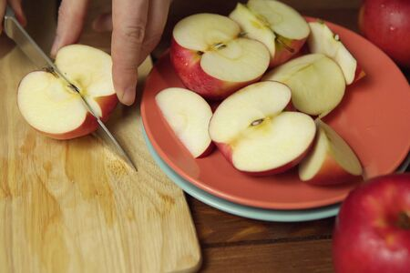 Hand with kitchen knife cuts half of ripe apple on light cutting board next to pink plate filled with pieces of apples.