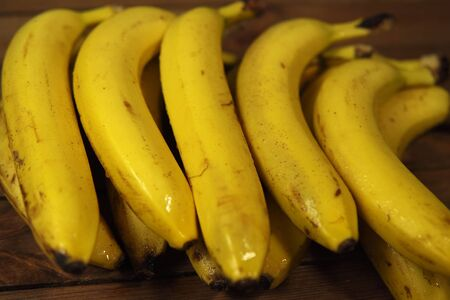 Close-up bunch of yellow ripe bananas with droplet water on wooden table, fruity background.