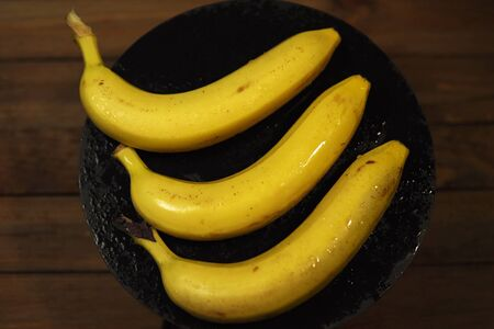 View from above on three ripe bananas with drops of water in a black plate on a wooden table.