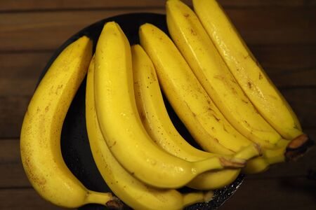Many ripe tasty bananas with water drops in black plate on wooden table.