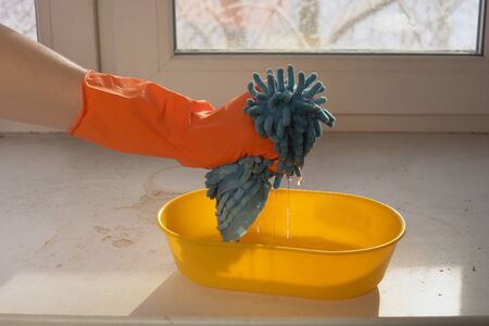 Woman's hand in orange glove squeezes blue microfiber cloth into yellow bowl with disinfectant solution on the windowsill on sunny day, preventing viral diseases and taking care of cleanliness. 写真素材