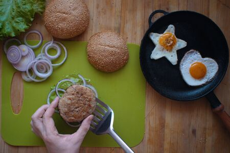 A top view of the process of cooking a hamburger at home, a man's hand puts a fried cutlet on half a bun, next to a star-shaped and heart-shaped fried eggs in the pan. 写真素材