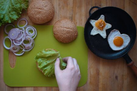 Top view of the process of cooking a hamburger at home, a man's hand puts a lettuce leaf on half of the bun, next to fried eggs in the shape of a star and a heart in a pan.