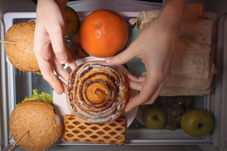 Top view of women's hands holding a sweet bun over the refrigerator shelf with burgers shawarma and fruit, flatlay.