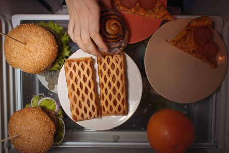 Top view on the shelf of the refrigerator, a human hand takes a sweet bun and puts it on a pink plate to a slice of pizza, the problem of improper nutrition.